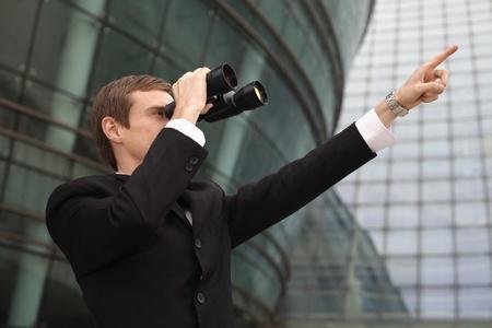 Businessman looking through binoculars and pointing ahead Standard-Bild