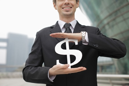 Businessman holding dollar sign Stock Photo - 13377843