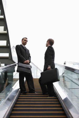 Businessmen talking on escalator photo