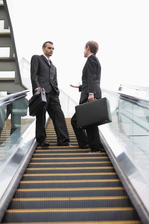 Businessmen talking on escalator photo