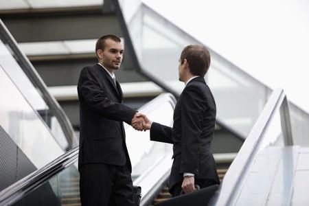 scandinavian descent: Businessmen shaking hands on escalator