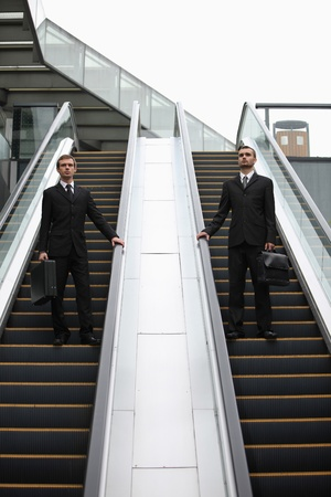 Businessmen with briefcase standing on escalator photo