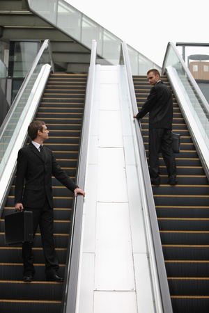 Businessmen looking at each other on escalator photo