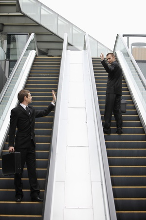 Businessmen waving at each other on escalator photo