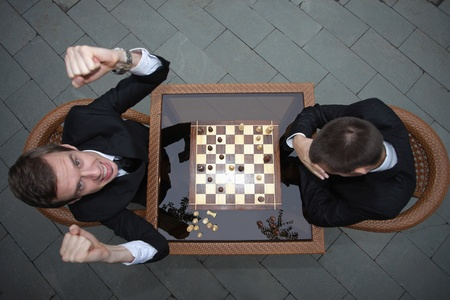 Businessmen playing chess outdoors, businessman cheering and raising fists photo