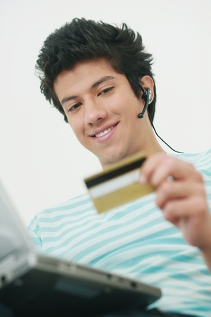 Man using laptop and credit card for home shopping photo