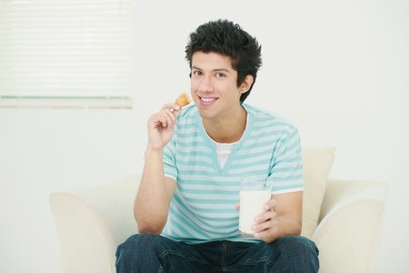 Man enjoying croissant with a glass of milk Stock Photo - 13383787