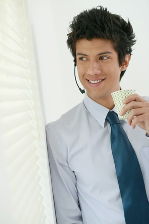 Businessman drinking water while looking out the window photo