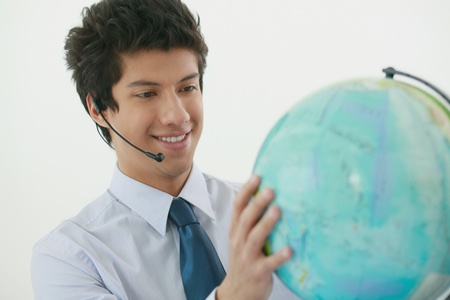 Businessman with headset holding a globe Stock Photo - 13383789