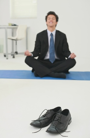 Businessman meditating in office Stock Photo - 13383772