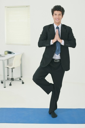 Businessman doing Tree pose in office photo