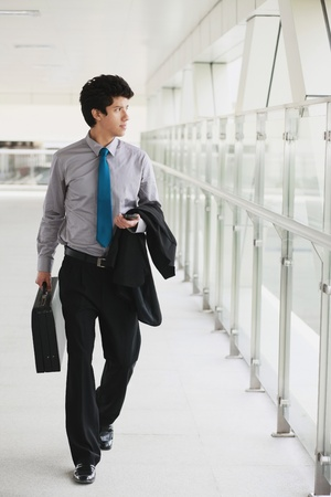 person walking: Businessman walking in a corridor Stock Photo
