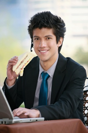 Businessman eating sandwich while using laptop photo