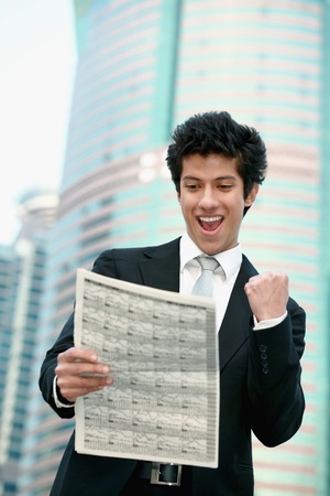 Businessman cheering while reading newspaper photo
