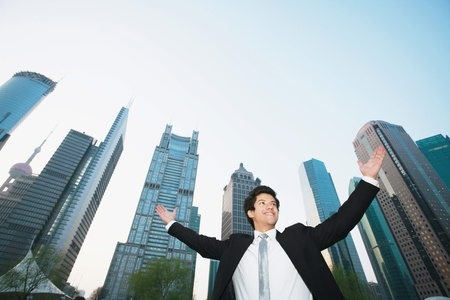 Businessman cheering with skyscrapers in the background photo