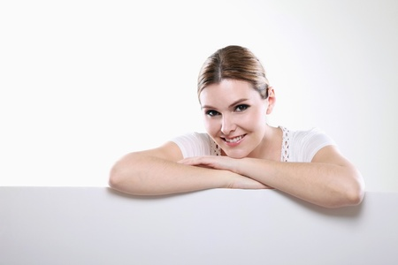 Woman with both arms resting on blank placard Stock Photo - 13383991