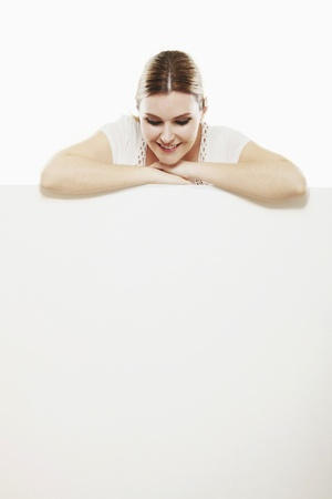 Woman with both arms resting on blank placard, looking down Stock Photo - 13383971