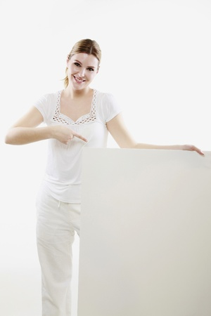 Woman pointing at blank placard Stock Photo - 13383981