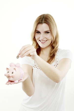 Woman putting a coin into piggy bank photo