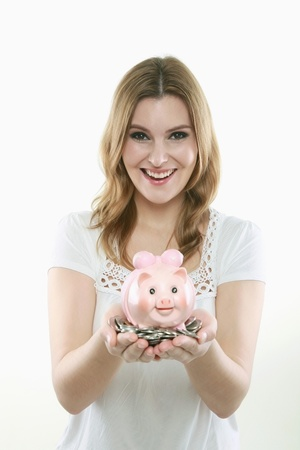 Woman holding a handful of coins and a piggy bank Stock Photo - 13384041