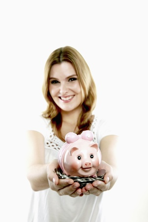 Woman holding a handful of coins and a piggy bank photo