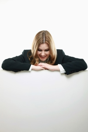 Businesswoman with both arms resting on blank placard, looking down Stock Photo - 13383978