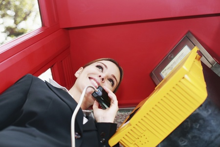 Businesswoman talking on the phone in telephone booth photo