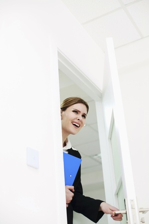 Businesswoman entering room with file in her hand photo