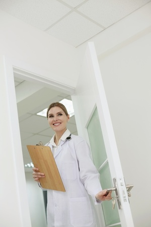 Doctor with clipboard entering a room photo