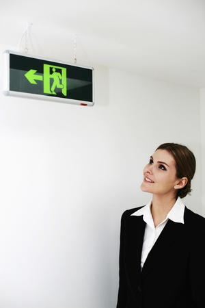 Businesswoman looking at exit sign in the building Stock Photo - 13384017