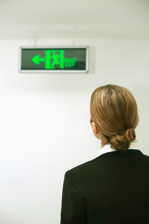 Businesswoman looking at exit sign in the building photo