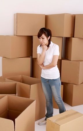 Woman looking at cardboard boxes, contemplating Stock Photo - 13384152