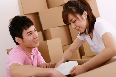 Man and woman packing plates into cardboard box photo
