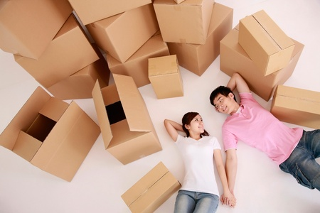 Man and woman lying down with moving boxes next to them