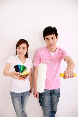Woman holding color swatch with man holding a paint roller beside her photo