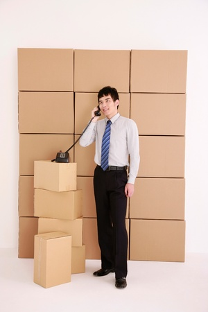 Businessman talking on the phone among stacked cardboard boxes Stock Photo - 13384173