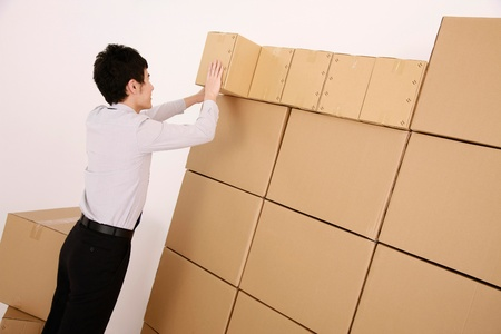 neatly: Businessman stacking cardboard boxes neatly