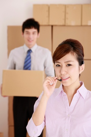 Businesswoman with headset and businessman carrying cardboard box in the background photo