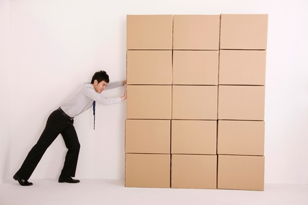Businessman trying to push cardboard boxes photo