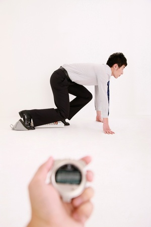 Human hand holding stopwatch with businessman crouching on starting block in the background photo