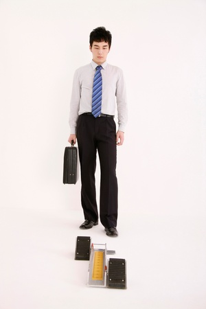 Businessman with briefcase standing in front of starting block photo