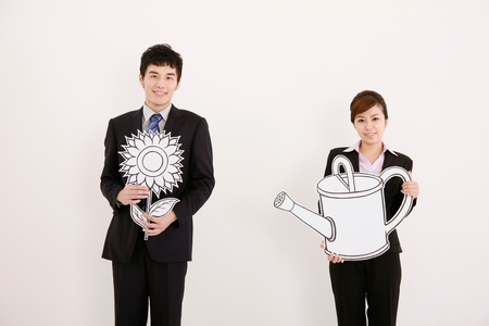 watering can: Businessman holding flower while businesswoman is holding a watering can