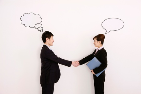 Business people with thought and speech bubble above their heads, shaking hands photo