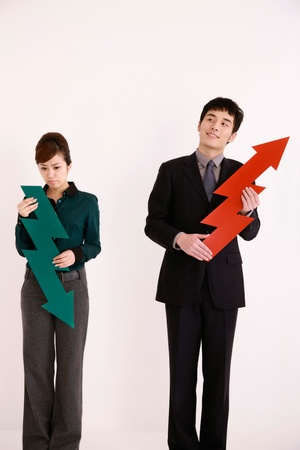Business people holding arrow signs Stock Photo