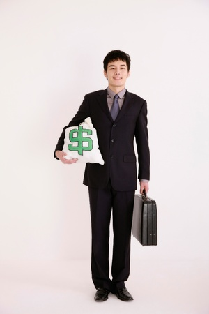 Businessman holding briefcase and money bag photo