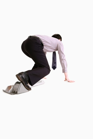 Businessman crouching on starting block Stock Photo