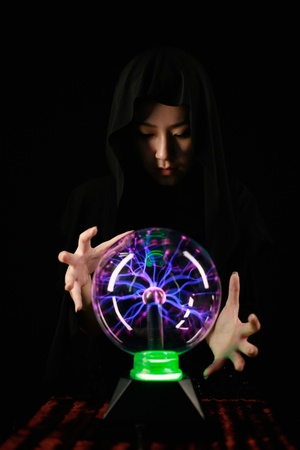 gazing: Woman with cape using crystal ball Stock Photo