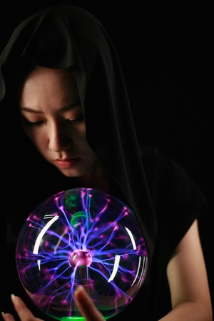 Woman with cape using crystal ball photo
