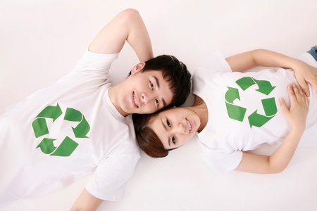 Man and woman wearing t-shirts with recycling symbol lying on the ground photo
