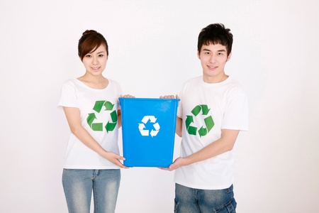 Man and woman holding recycling bin photo